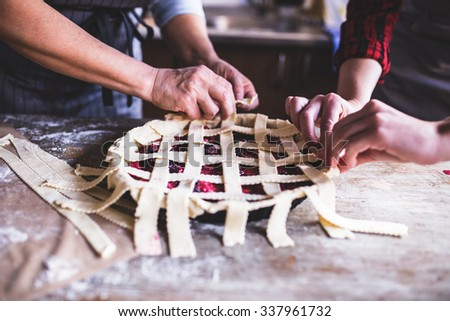 Mother and daughter making Delicious Cherry Pie, wooden table, depth of field   - stock photo