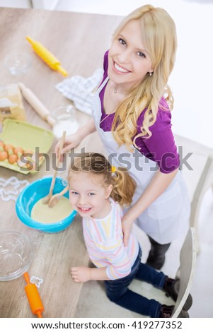 Mother and daughter mixing dough together - stock photo