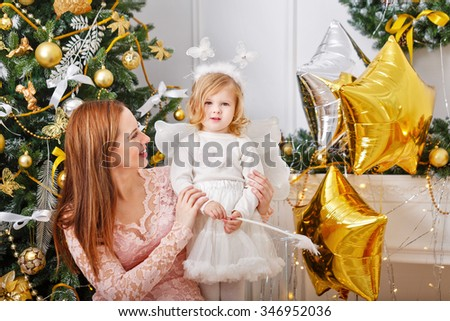 Mother and daughter near Christmas tree. Girl dressed as a snowflake. New Year. Family celebration. Holiday and fun. Merry Christmas. - stock photo