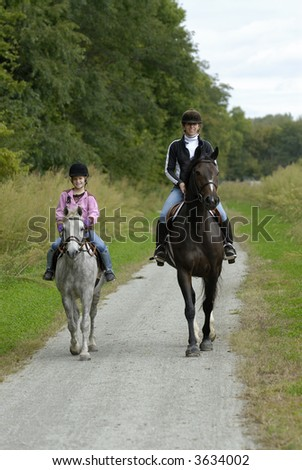 Mother and daughter on a trail ride with pony and horse. - stock photo