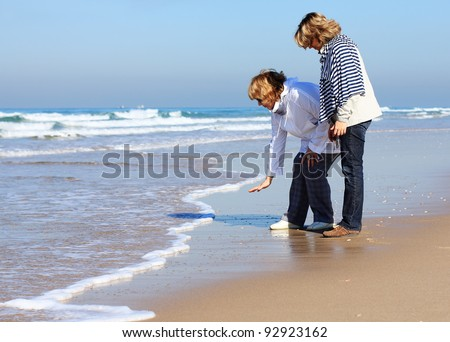 Mother and daughter on a winter beach - stock photo