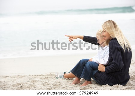 Mother And Daughter On Holiday Sitting On Winter Beach