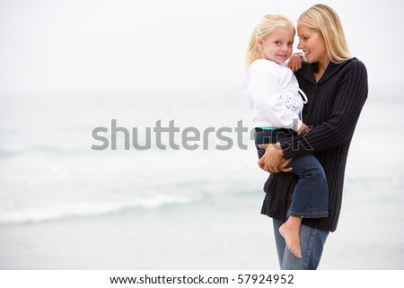 Mother And Daughter On Holiday Standing On Winter Beach