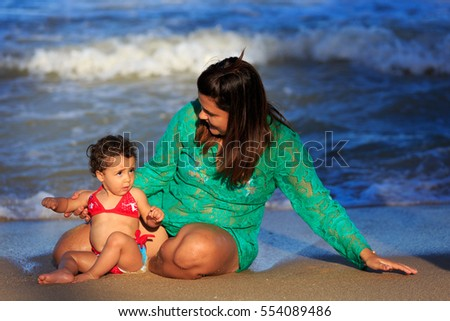 Mother and daughter on the beach playing in the water