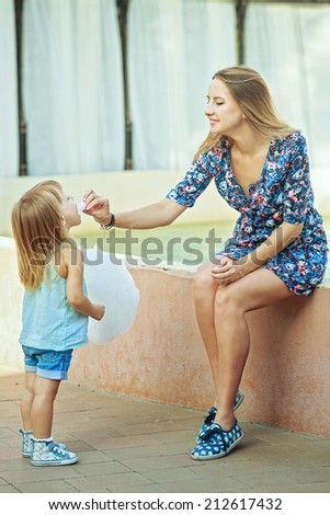 Mother and daughter on the walk in the city park. A mother feeds her daughter cotton candy. - stock photo