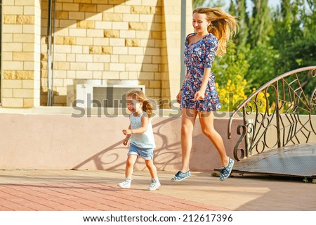Mother and daughter on the walk in the city park. The child runs away from her mother. - stock photo