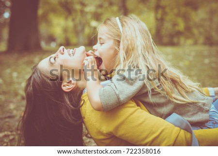 Mother and daughter outdoors in a meadow. Little girl sitting on mother lap and tick her mother.