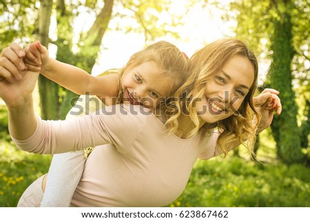 Mother and daughter outdoors in a meadow. Mother carrying her daughter on piggyback. Looking at camera.