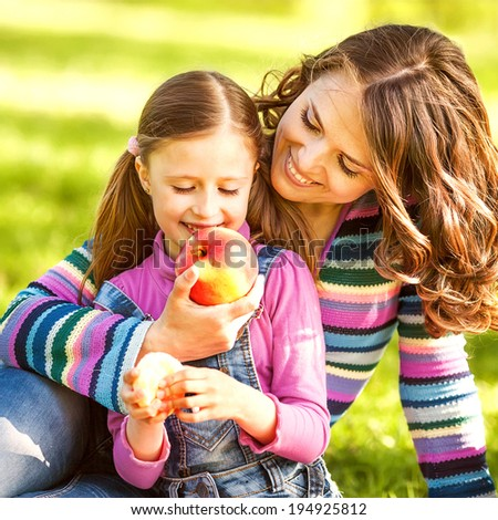 mother and daughter outdoors on a picnic eat apple - stock photo