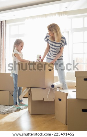 Mother and daughter packing cardboard boxes at home - stock photo