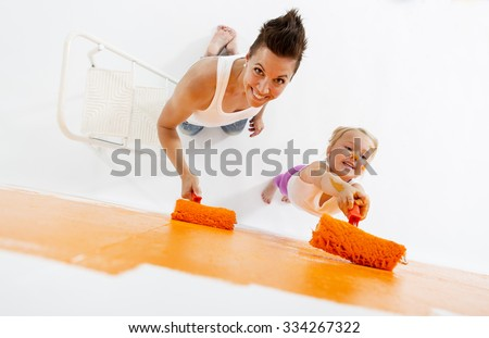 Mother and daughter painting a wall together - stock photo