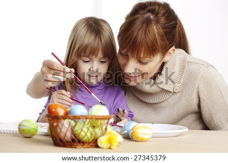 mother and daughter painting eggs - stock photo