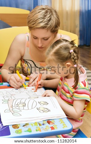 mother and daughter painting in a children's room