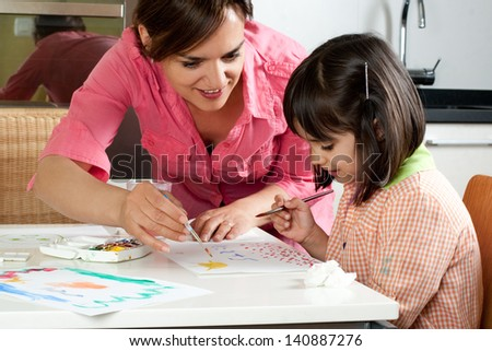 Mother and daughter painting together at home with paintbrushes and watercolors - stock photo