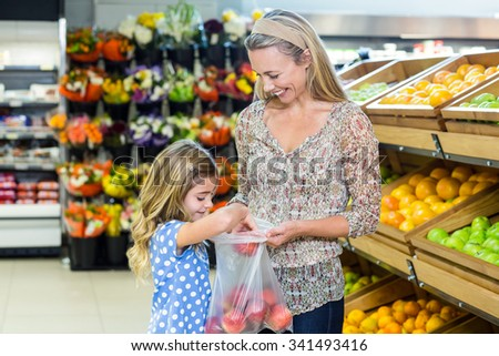 Mother and daughter picking out apple in supermarket - stock photo