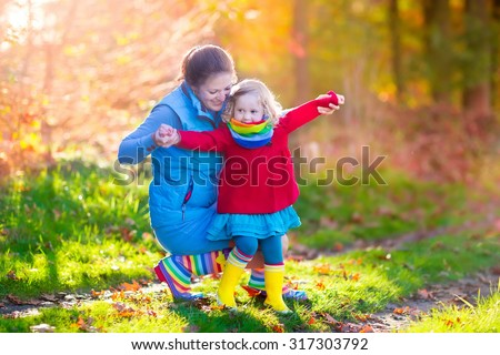 Mother and daughter play in autumn park. Parent and child walk in the forest on a sunny fall day. Children playing outdoors with yellow maple leaf. Toddler girl picking golden leaves. Mom hugging kid - stock photo