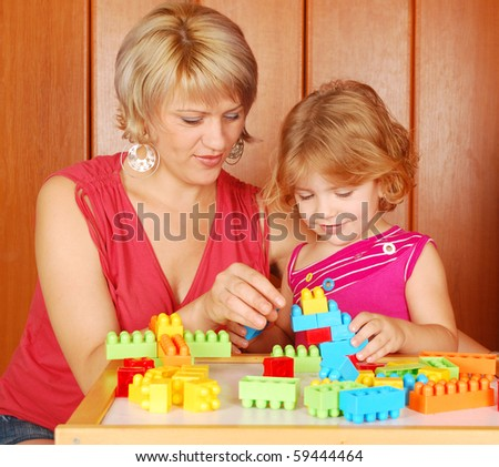 mother and daughter play with toy brick