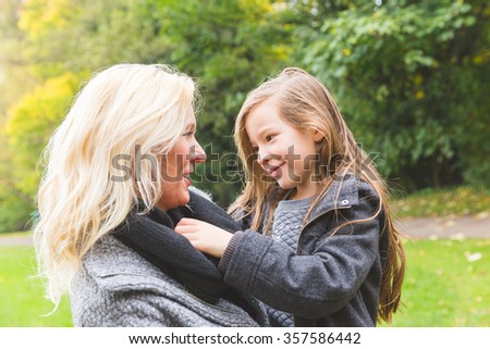 Mother and daughter playing and looking each other at park in autumn. The mother is caucasian and she is carrying her mixed race daughter on her arms. Family lifestyle concept. - stock photo