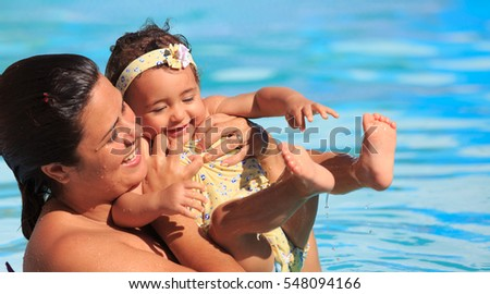 Mother and Daughter Playing and Swimming in a Pool