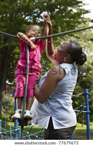 Mother and daughter playing at a park - stock photo