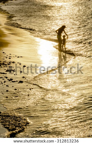 Mother and daughter playing at the seashore during sunset on the beach of the Armação in Buzios, Rio de Janeiro - stock photo