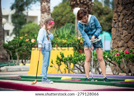 Mother and daughter playing golf on a golf course - stock photo