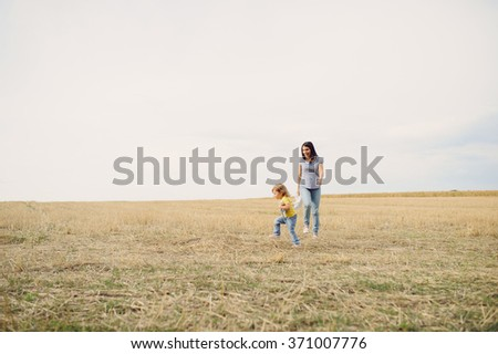 mother and daughter playing in field - stock photo
