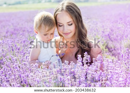 Mother and daughter playing in lavender field on beautiful summer day - stock photo