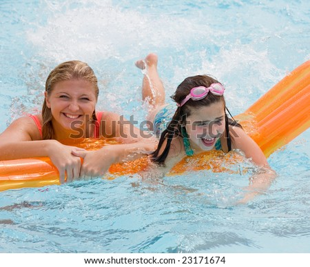 Mother and Daughter Playing in the Pool - stock photo