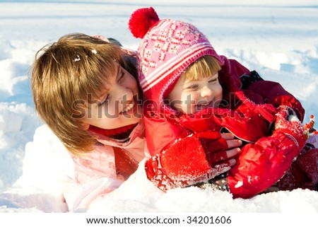 Mother and daughter playing in the snow - stock photo