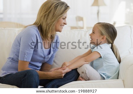 Mother and daughter playing on couch - stock photo