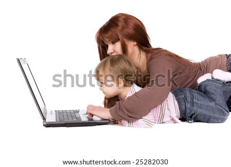 mother and daughter playing on laptop - stock photo