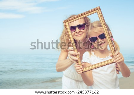 Mother and daughter playing on the beach at the day time. Concept of friendly family. - stock photo