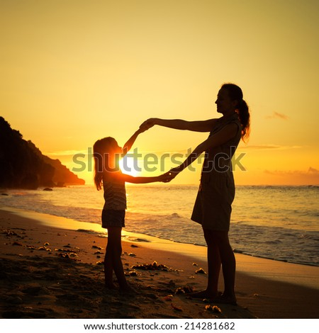 mother and  daughter playing on the beach at the sunrise time - stock photo
