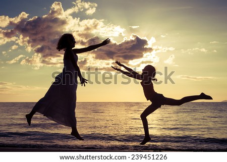 mother and  daughter playing on the beach at the sunset time