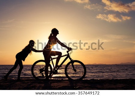 mother and daughter playing on the beach at the sunset time. Concept of friendly family. - stock photo