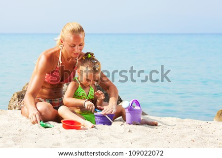 Mother and daughter playing on the beach with bucket and spade