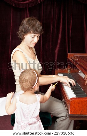 Mother and daughter playing piano - stock photo