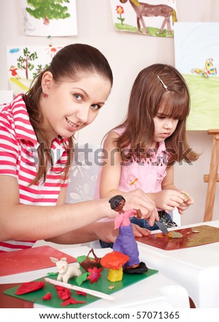 Mother and  daughter playing  plasticine. Child care. - stock photo