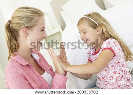 Mother And Daughter Playing Together In Bedroom - stock photo