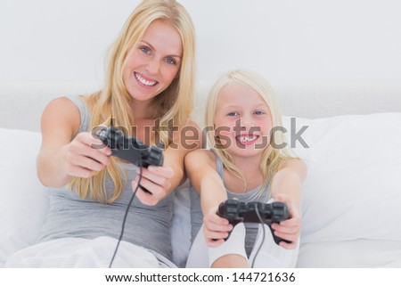 Mother and daughter playing video games in bed