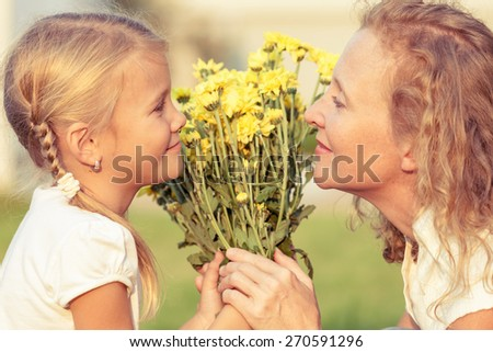 Mother and daughter playing with flowers on the grass at the day time. Concept of friendly family. - stock photo