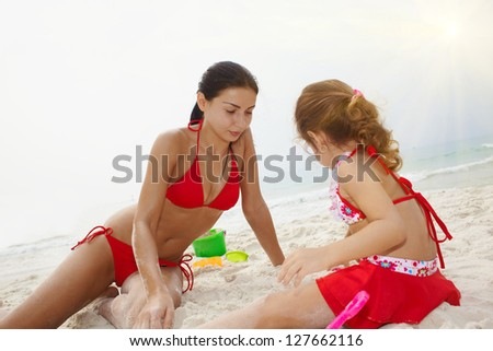 Mother and daughter playing with sand on sea coast - stock photo