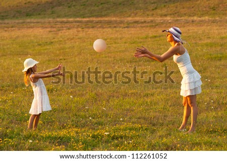 Mother and daughter playing with the ball on the meadow on beautiful summer day. - stock photo