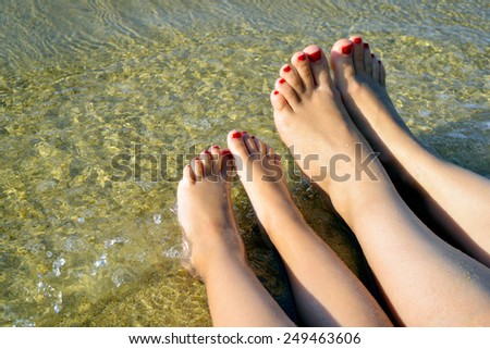 Mother and daughter playing with their legs in the water at beach - stock photo
