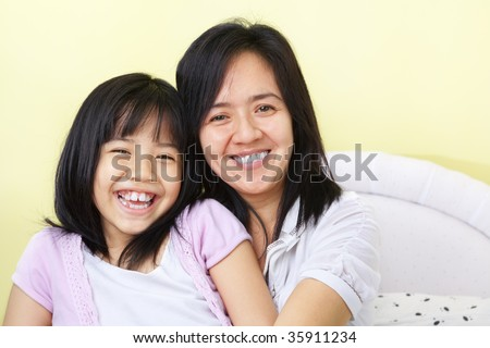 Mother and daughter posing happily to camera - stock photo