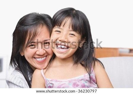 Mother and daughter posing together in the living room - stock photo