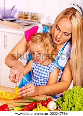 Mother and daughter prepare at kitchen..