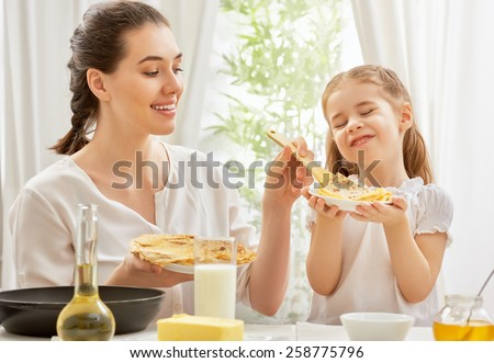 mother and daughter prepare pancakes - stock photo