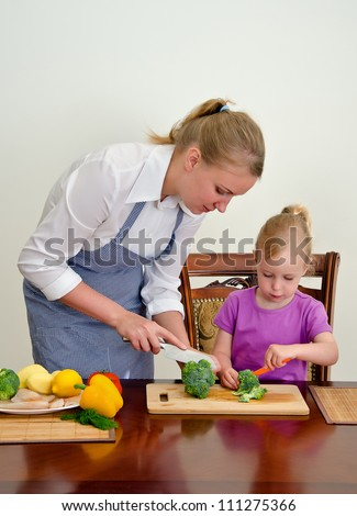 Mother and daughter preparing food. Cutting broccoli with knife. - stock photo